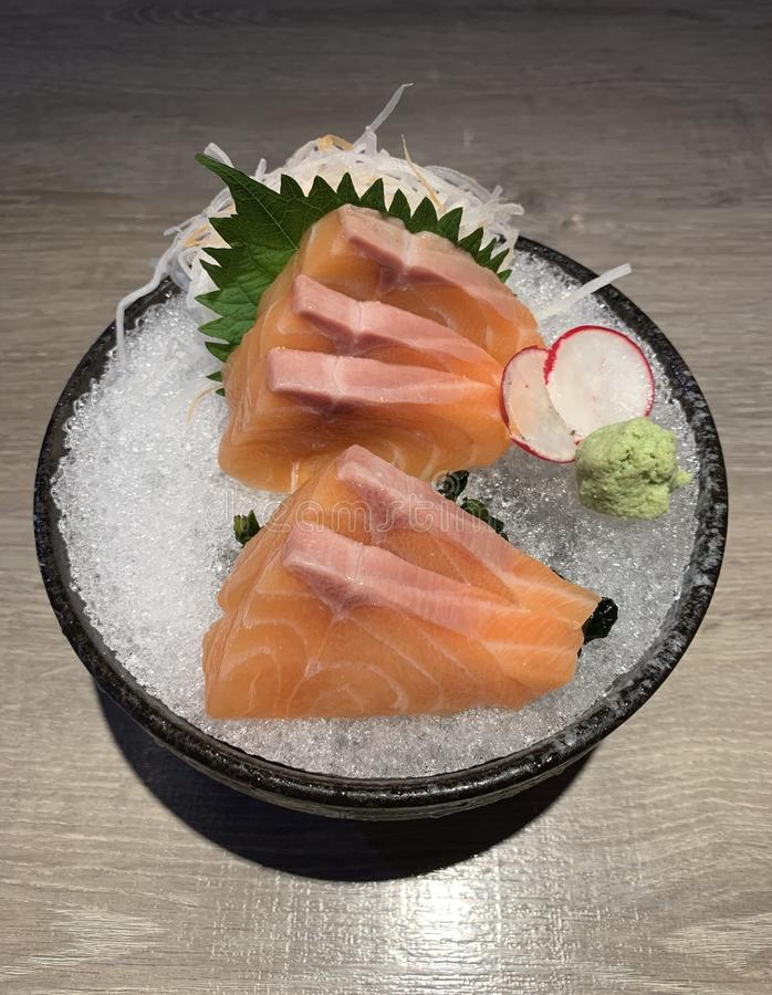 Raw salmon slice or salmon sashimi in Japanese style fresh serve on ice with fresh wasabi royalty free stock photos