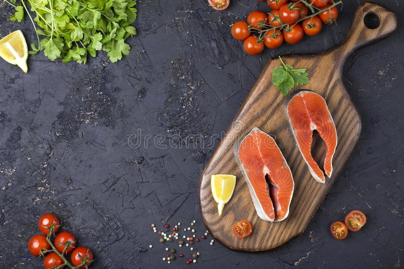 Raw salmon steak with herbs, parsley and lemon royalty free stock photos