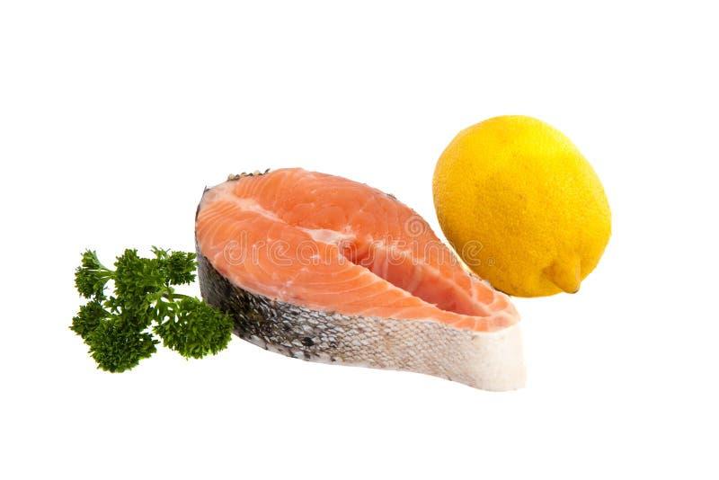 Raw salmon steak, lemon and parsley royalty free stock images