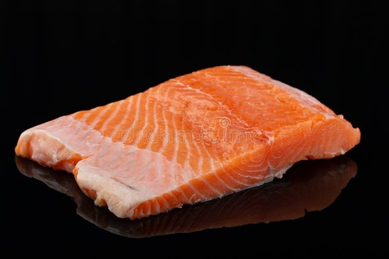 Raw salmon steak meat on black background. Fresh Raw salmon steak meat on black background stock image