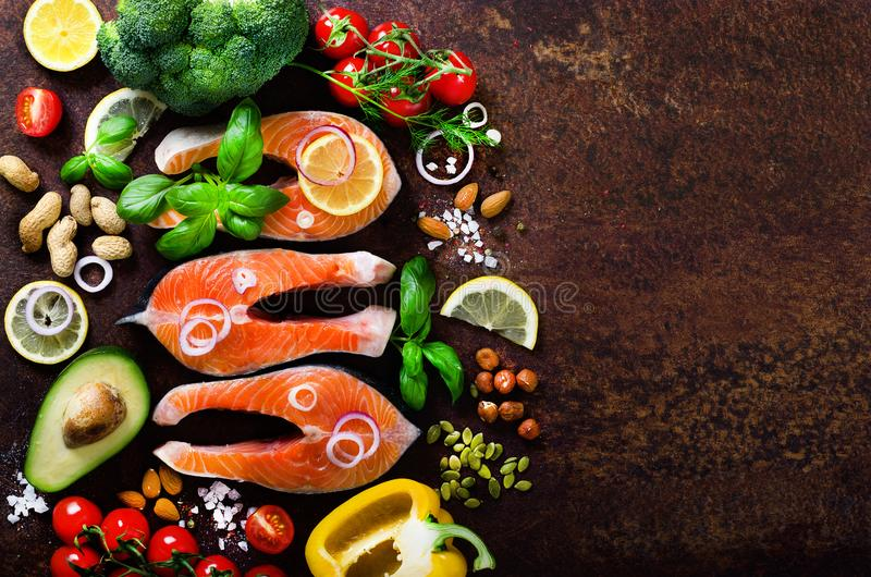 Raw salmon steaks, aromatic herbs, onion, lemon, salt and fresh vegetables for cooking on wooden background. Copyspace royalty free stock photos