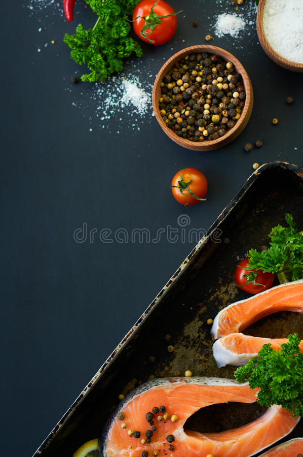 Raw salmon steaks on a dark background stock images