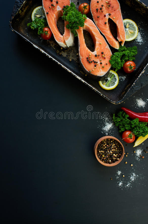 Raw salmon steaks on a dark background royalty free stock photo