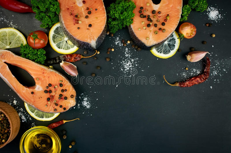 Raw salmon steaks on a dark background royalty free stock image