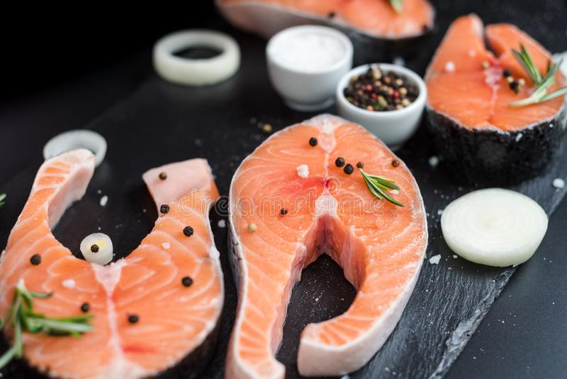 Raw salmon steaks on the dark stone background royalty free stock photos