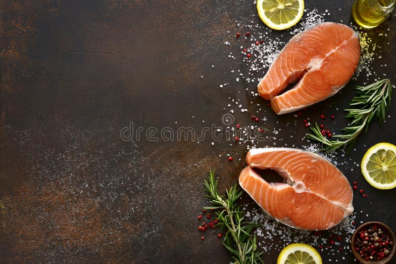 Raw salmon steaks marinated with lemon, rosemary, spices and olive oil.Top view with copy space stock photos