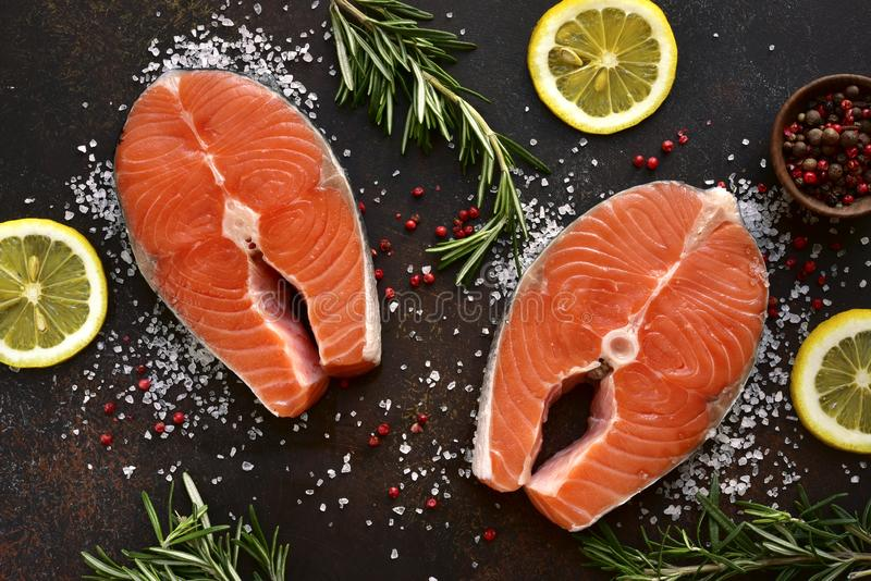 Raw salmon steaks marinated with lemon, rosemary, spices and olive oil.Top view with copy space royalty free stock photo