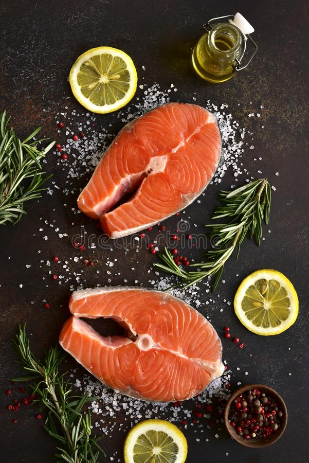 Raw salmon steaks marinated with lemon, rosemary, spices and olive oil.Top view with copy space royalty free stock images