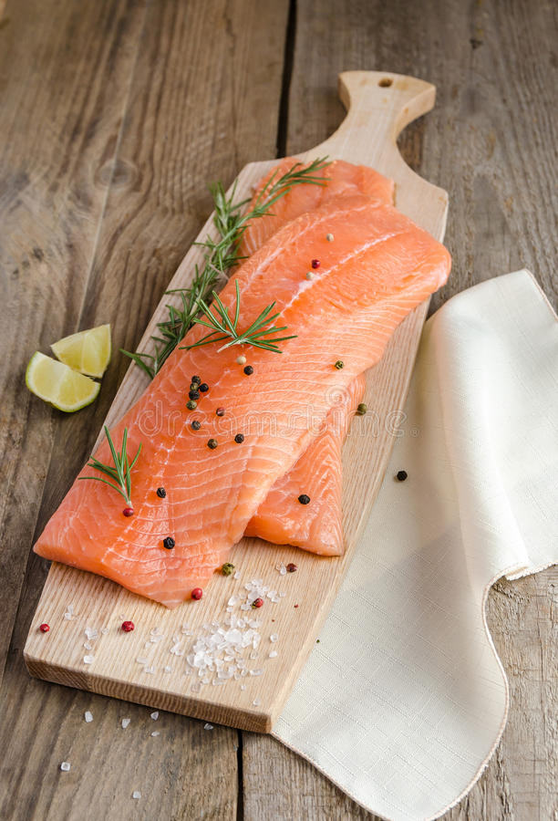 Raw salmon steaks on the wooden board stock photography