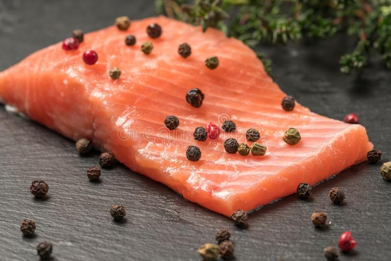 Raw salmon, trout fillet on a dark slate background. Wild atlantic fish. Healthy food stock photos