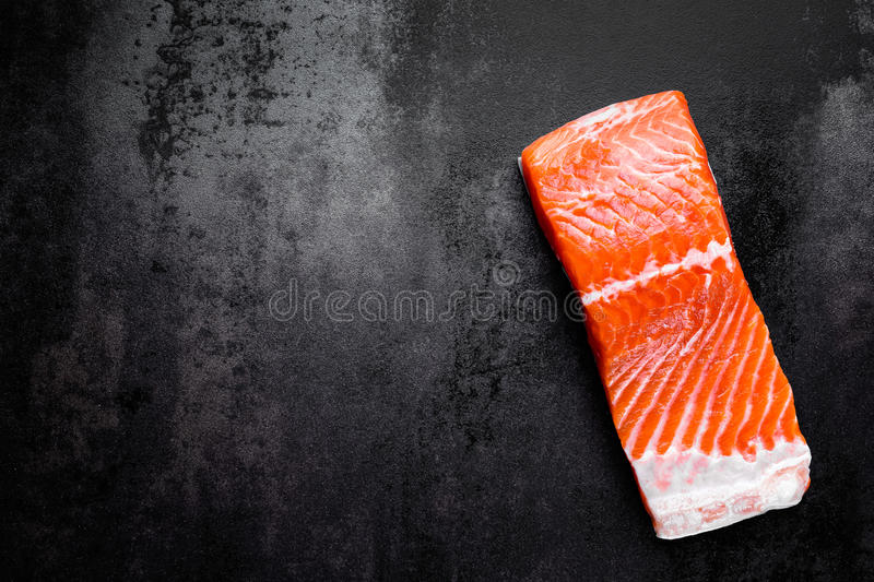Raw salmon or trout sea fish fillet on black metal background, top view royalty free stock image