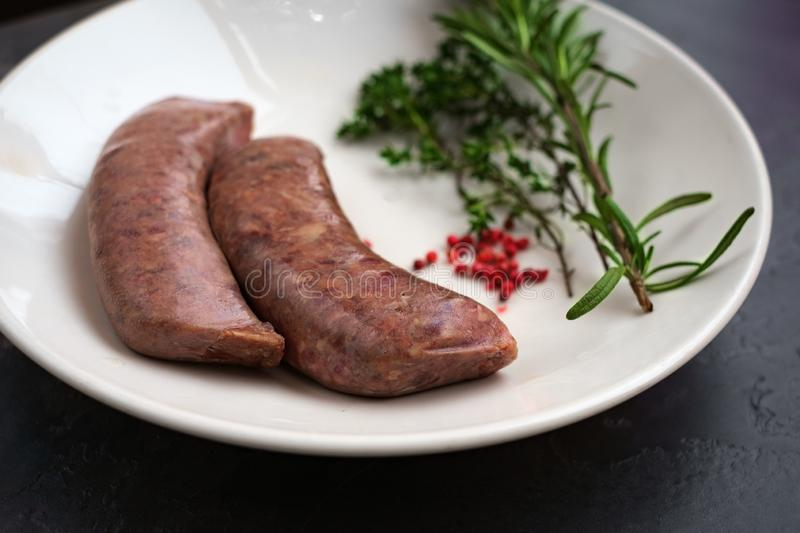 Raw sausages for grilling on a plate. Raw pork sausages for grilling in a white plate on a stone background stock photos
