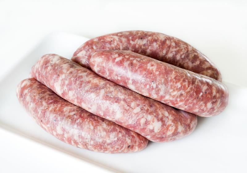 Raw sausages. Raw homemade pork sausages on a white plate, closeup shot royalty free stock images