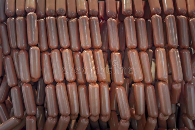 Raw sausages links on racks in storage room at meat processing factory royalty free stock image