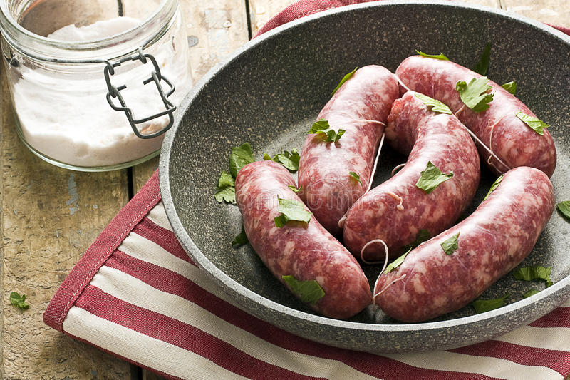 Raw Sausages in a Pan. Raw sausages in a black pan with herbs next to salt on rustic wooden table stock images