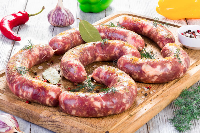 Raw sausages prepared for grill with chilli pepper, garlic stock photography