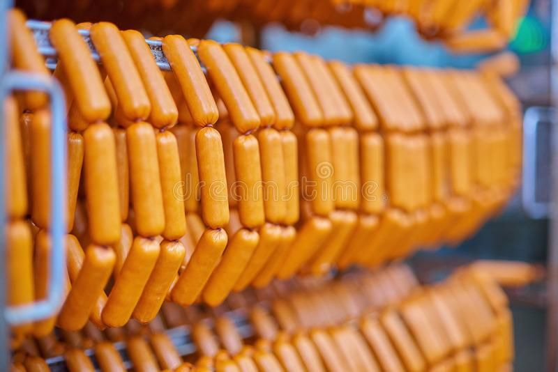 Raw sausages on racks in storage room at meat processing factory royalty free stock photography
