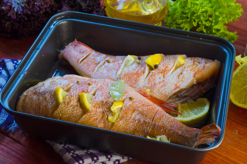 Raw sea bass in a baking. Raw sea bass in a pan ready for baking stock photography