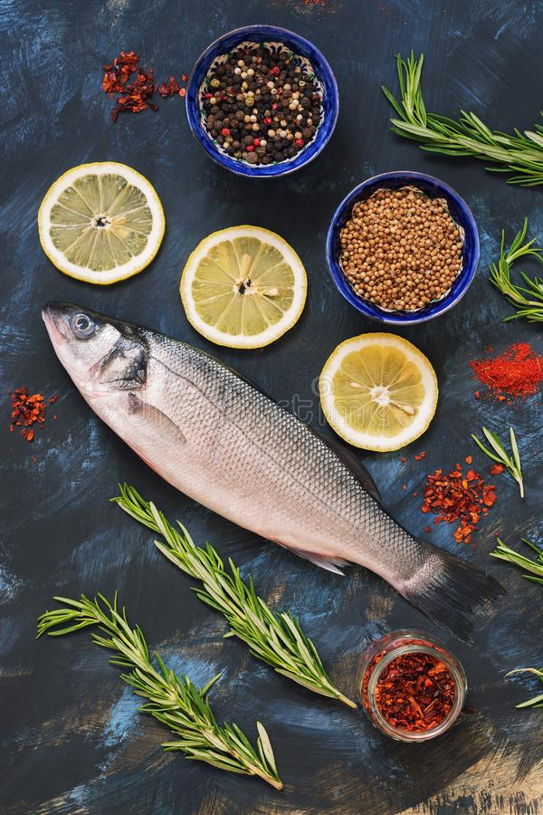 Raw sea bass fish on blue abstract background with lemon and spices. stock photos