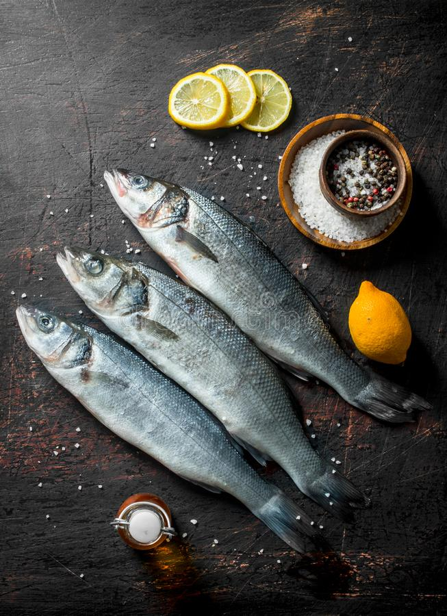Raw sea bass fish with sliced lemon and spices. On dark rustic background stock photos