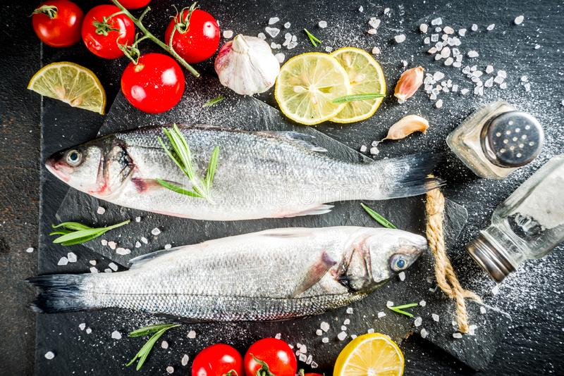 Raw sea bass fish with spices. And ingredients, ready for cooking, dark concrete background copy space royalty free stock photos