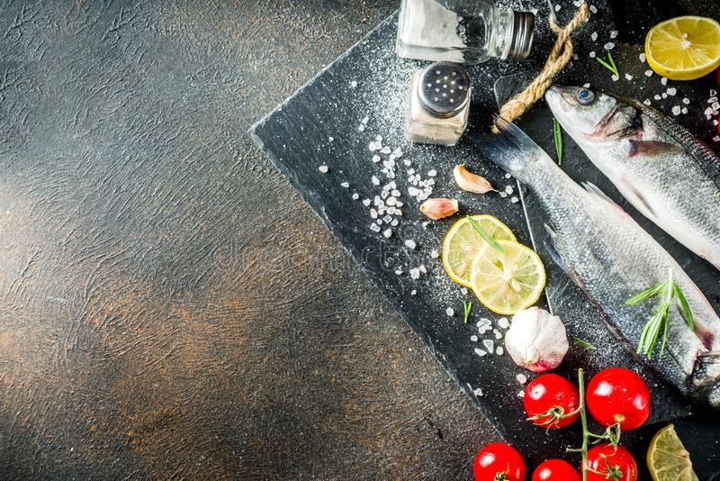 Raw sea bass fish with spices. And ingredients, ready for cooking, dark concrete background copy space royalty free stock images