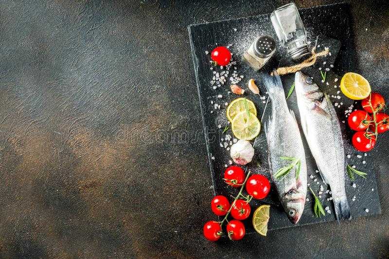 Raw sea bass fish with spices. And ingredients, ready for cooking, dark concrete background copy space stock images