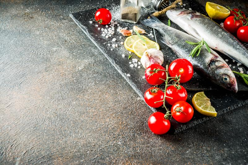 Raw sea bass fish with spices. And ingredients, ready for cooking, dark concrete background copy space stock photography