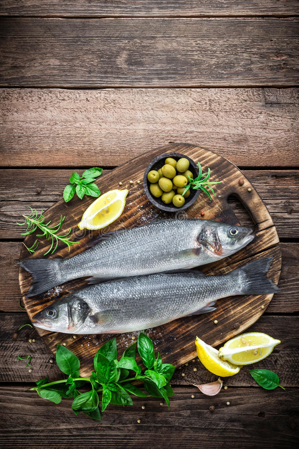 Raw sea bass fish. On wooden background top view royalty free stock photo