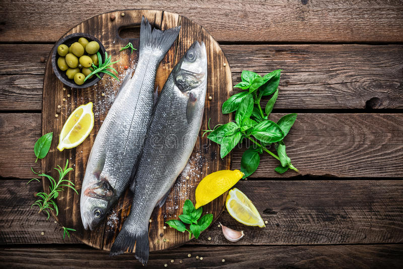 Raw sea bass fish. On wooden background top view royalty free stock photography