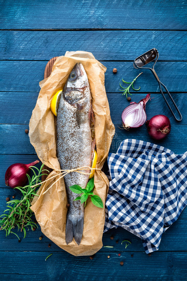 Raw sea bass fish. On wooden background top view stock image