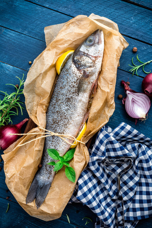 Raw sea bass fish. On wooden background top view royalty free stock images