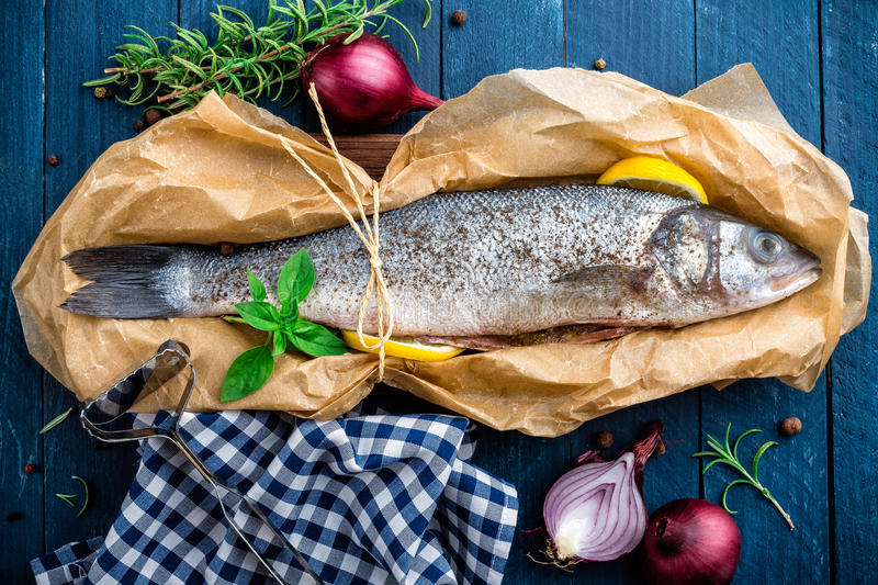 Raw sea bass fish. On wooden background top view stock photography