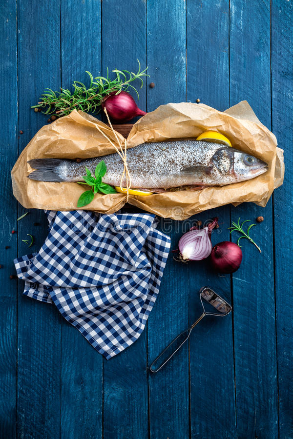 Raw sea bass fish. On wooden background top view stock photo