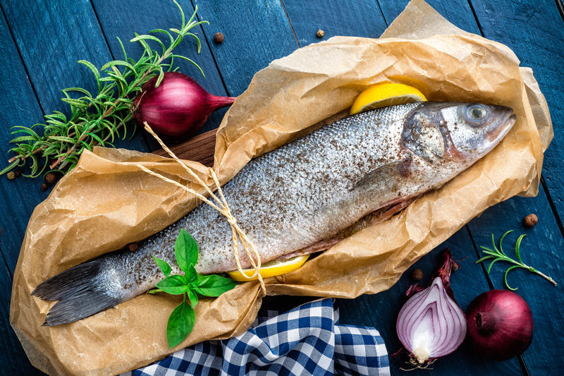 Raw sea bass fish. On wooden background top view stock images