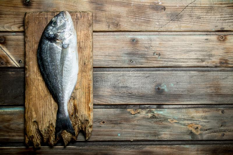 Raw sea fish dorado on a cutting Board. On a wooden background royalty free stock photos