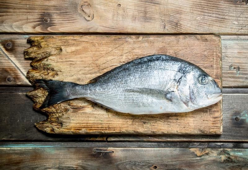 Raw sea fish dorado on a cutting Board. On a wooden background stock photo