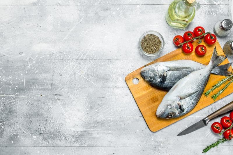 Raw sea fish dorado with spices and tomatoes. On a rustic background royalty free stock images