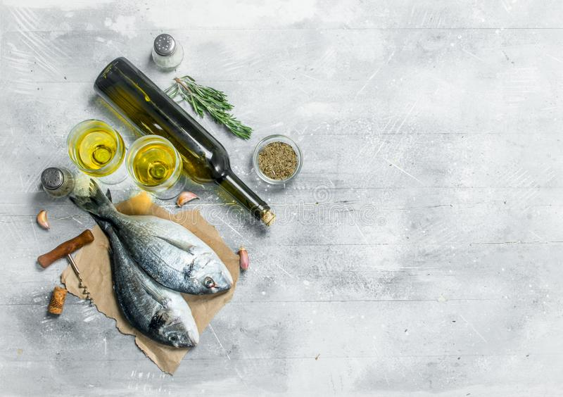 Raw sea fish dorado with white wine and spices. On a rustic background royalty free stock images