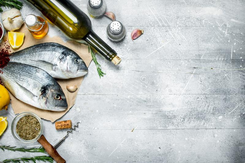 Raw sea fish dorado with white wine and spices. On a rustic background stock images