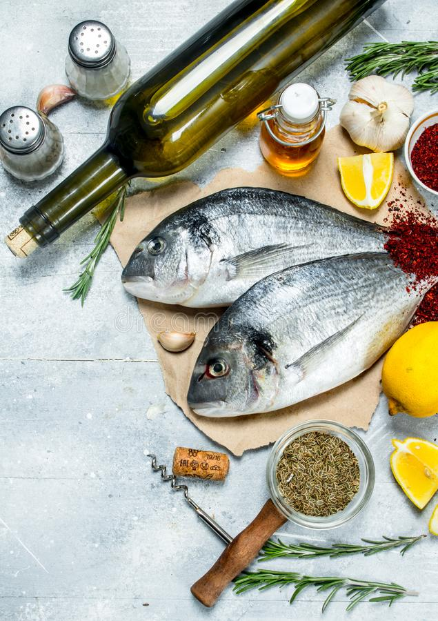 Raw sea fish dorado with white wine and spices. On a rustic background royalty free stock image