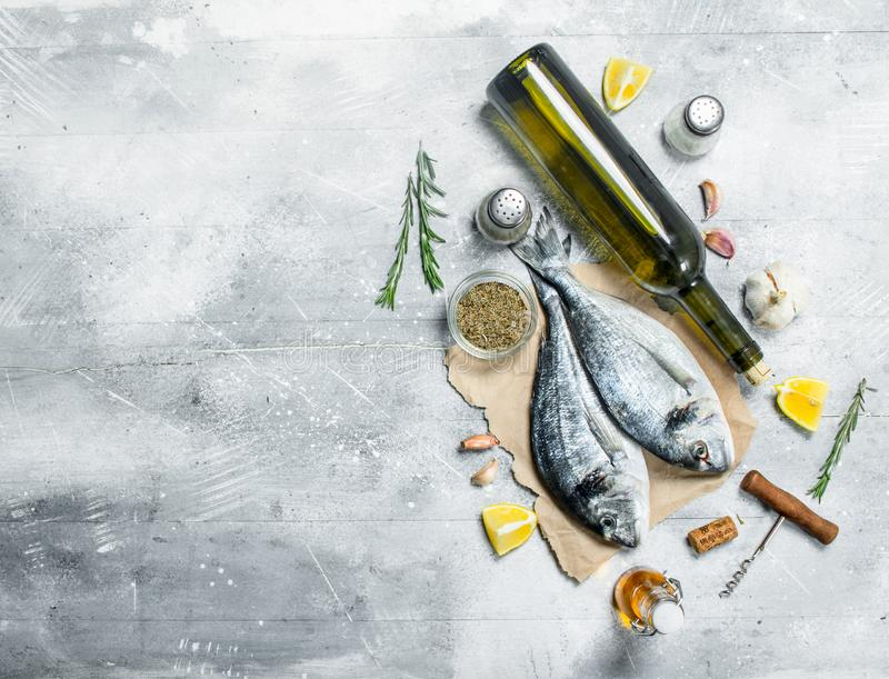 Raw sea fish dorado with white wine and spices. On a rustic background royalty free stock photo