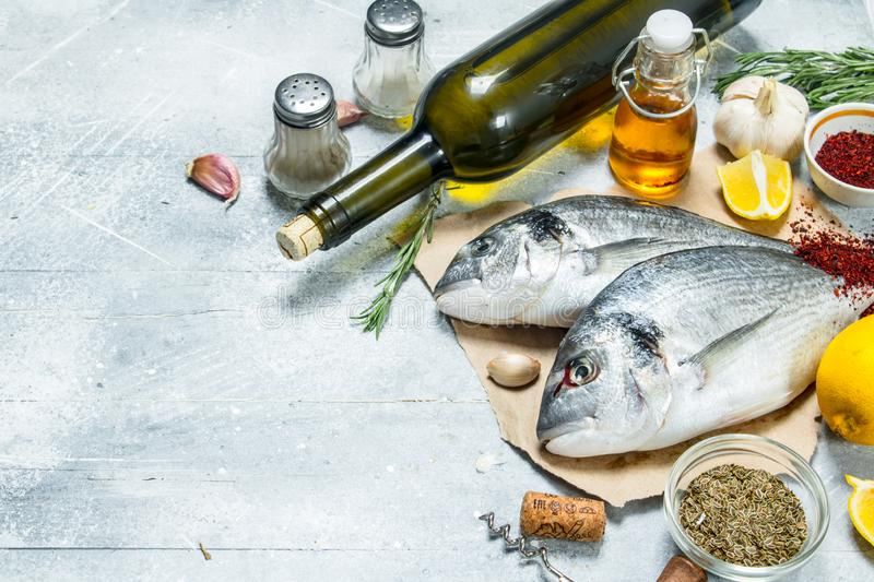 Raw sea fish dorado with white wine and spices. On a rustic background stock photo