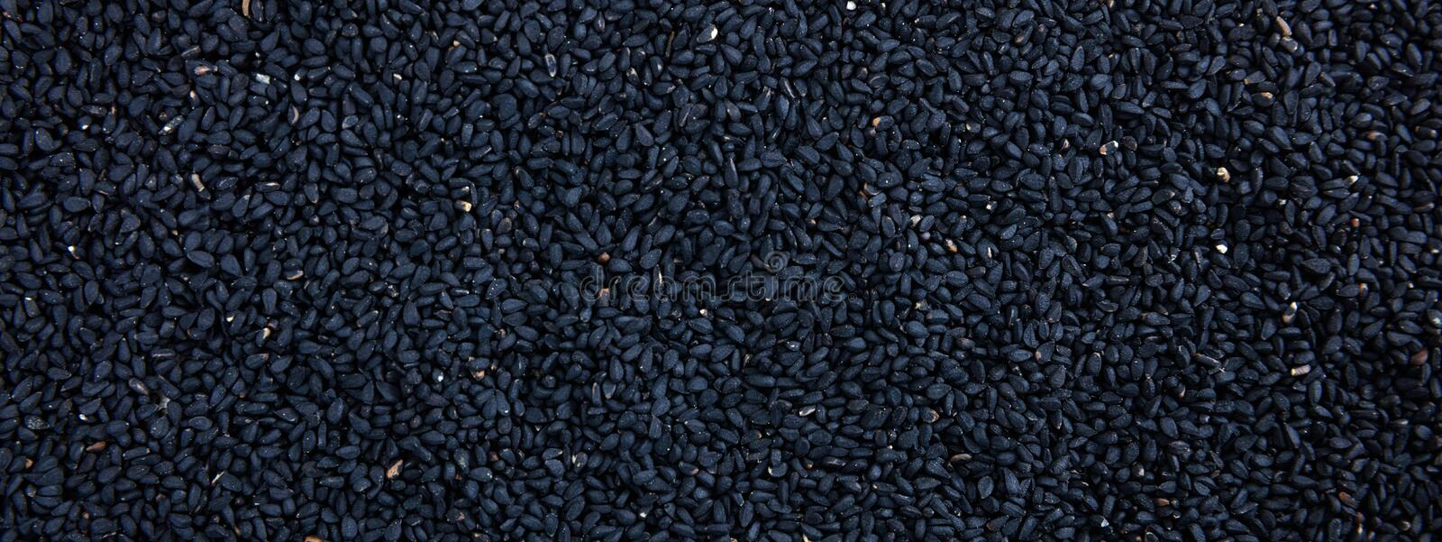 Raw sesame seeds black color full frame background, banner. Raw sesame dry grains black color full frame background, banner. Close up top view royalty free stock photography