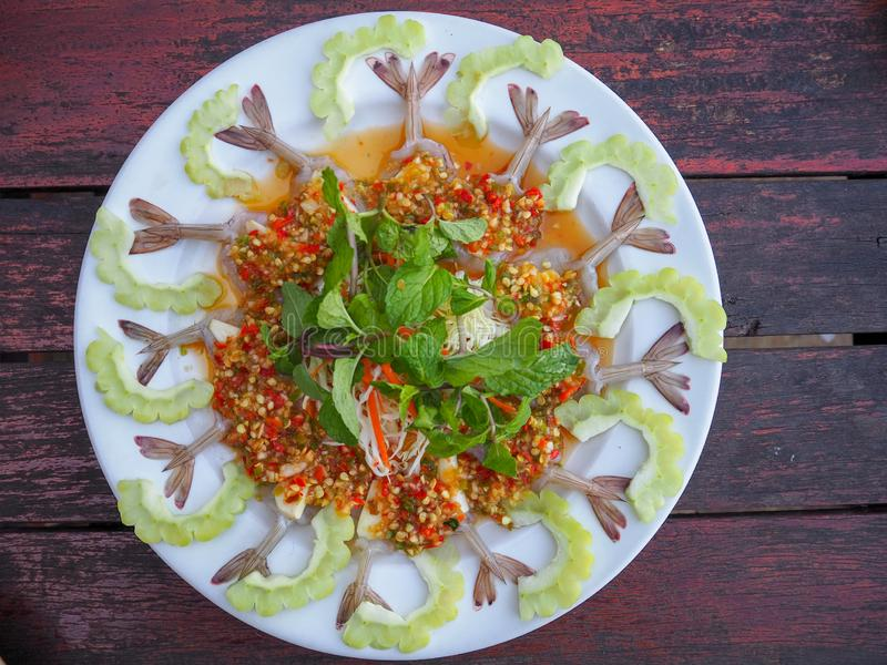Raw shrimp with spicy sauce on a white round plate, Shrimp and Chinese bitter gourd beautifully placed alternately. Sprinkle top g royalty free stock image