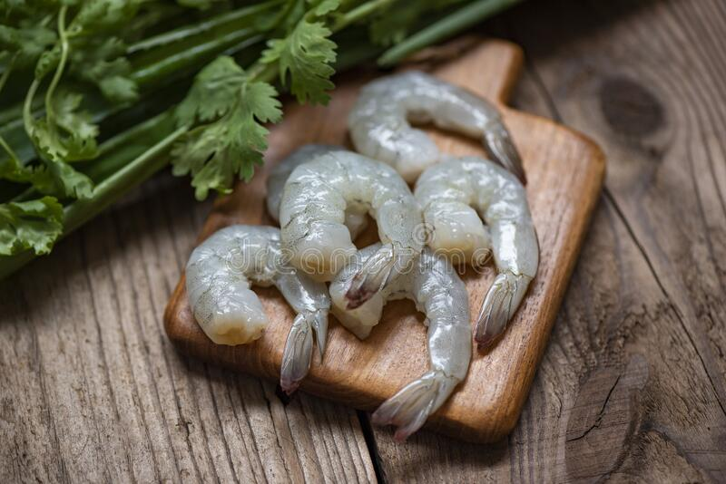 Raw shrimp on wooden cutting board background for cooking - close up fresh shrimps or prawns , Seafood shelfish stock image