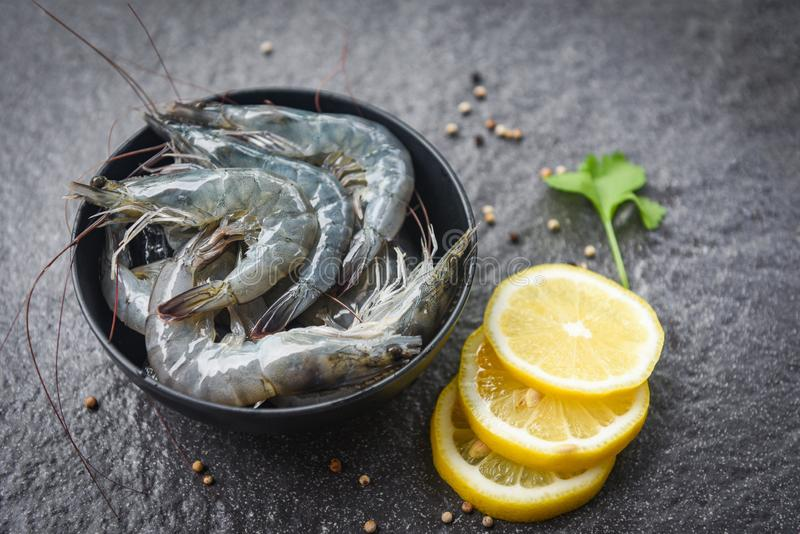 Raw shrimps on bowl - fresh shrimp prawns for cooking with spices lemon and celery on dark background in the seafood restaurant royalty free stock image
