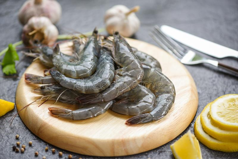 Raw shrimps on wooden cutting board plate fresh shrimp prawns for cooking with spices lemon and celery garlic on dark background royalty free stock image