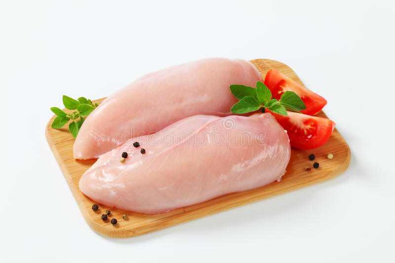 Raw skinless chicken breast fillets. On cutting board stock image