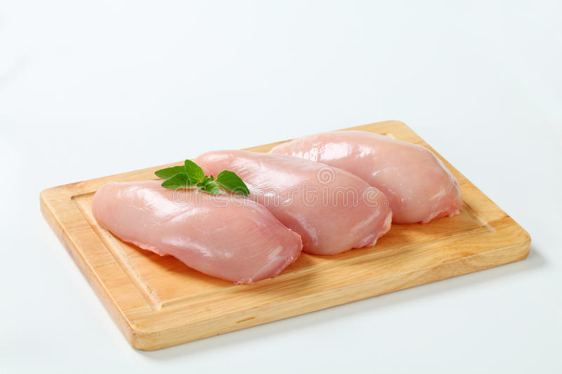 Raw skinless chicken breast fillets. On cutting board royalty free stock image